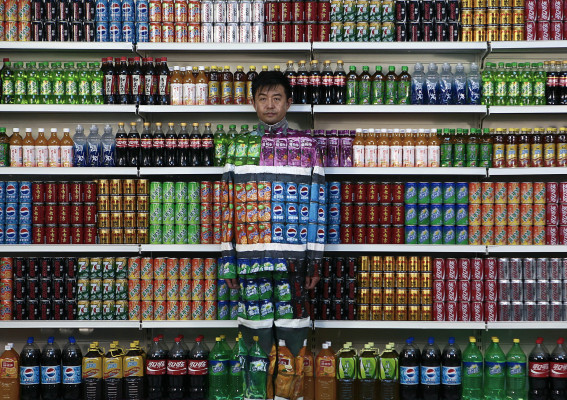 "Chinese artist Liu Bolin waits for his colleagues to put a finishing touch on him to blend into rows of soft drinks in his artwork entitled ""Plasticizer"" to express his speechlessness at use of plasticizer in food additives, in his studio at the 798 Art District in Beijing, China, Wednesday, Aug. 10, 2011. (AP Photo)"